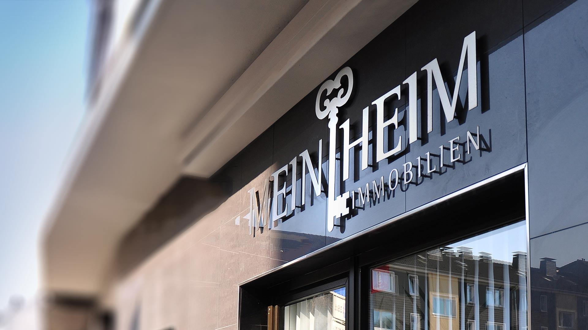 Das Aluminium Logo an der Außenfassade passend zum Corporate Design von MeinHeim Immobilien
